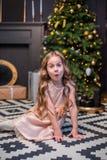 Niña bajo el árbol de navidad Una muchacha con los regalos debajo del árbol antes de magia foto de archivo