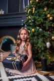 Niña bajo el árbol de navidad Una muchacha con los regalos debajo del árbol antes de magia imagen de archivo