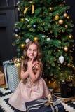 Niña bajo el árbol de navidad Una muchacha con los regalos debajo del árbol antes de magia imagenes de archivo