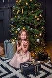 Niña bajo el árbol de navidad Una muchacha con los regalos debajo del árbol antes de magia imágenes de archivo libres de regalías