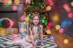 Niña bajo el árbol de navidad Una muchacha con los regalos debajo del árbol antes de magia fotos de archivo
