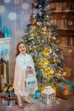 Niña bajo el árbol de navidad Una muchacha con los regalos debajo del árbol antes de magia fotografía de archivo