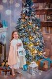Niña bajo el árbol de navidad Una muchacha con los regalos debajo del árbol antes de magia imagen de archivo libre de regalías