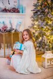 Niña bajo el árbol de navidad Una muchacha con los regalos debajo del árbol antes de magia foto de archivo libre de regalías