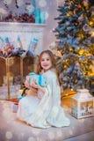 Niña bajo el árbol de navidad Una muchacha con los regalos debajo del árbol antes de magia fotografía de archivo libre de regalías