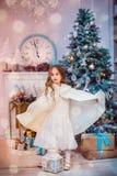 Niña bajo el árbol de navidad Una muchacha con los regalos debajo del árbol antes de magia fotos de archivo libres de regalías