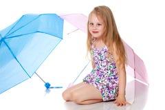Niña bajo un paraguas fotos de archivo