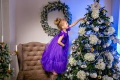 Niña bonita 4 años en un vestido azul Bebé en sitio de la Navidad con el reloj teddybear, grande, árbol de navidad, butaca marrón fotografía de archivo libre de regalías