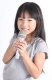 Niña bonita con el micrófono en su mano Foto de archivo