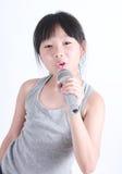 Niña bonita con el micrófono en su mano Fotografía de archivo