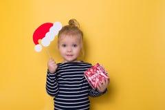 Niña bonita con el sombrero de santa y la caja de regalo en backgro amarillo Fotos de archivo libres de regalías