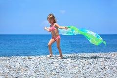 Niña bonita con la tela en la costa pedregosa Foto de archivo libre de regalías