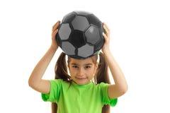 Niña bonita en camisa verde con el balón de fútbol en manos Fotos de archivo libres de regalías