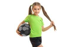 Niña bonita en camisa verde con el balón de fútbol en manos Imagen de archivo