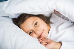 Niña bonita en la ropa de noche que miente debajo de la manta en la cama en casa imagenes de archivo