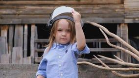 Niña bonita en ropa elegante en el casco protector del bombero almacen de metraje de vídeo