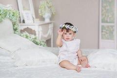Niña bonita en un vestido blanco y con una diadema en una cabeza en un dormitorio Foto de archivo