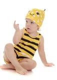 Niña bonita en una sentada rayada de la abeja del traje Imágenes de archivo libres de regalías