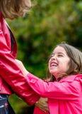 Niña bonita feliz que juega con su madre Foto de archivo