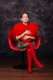 Niña bonita que lleva el vestido hermoso que se sienta en butaca roja Ella está llevando a cabo el corazón de la felpa en manos T Fotos de archivo libres de regalías