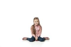 Niña bonita que se sienta en el suelo en pantalones vaqueros Imagen de archivo libre de regalías