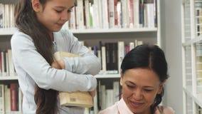 Niña bonita que sonríe mientras que su mamá que lee un libro en la biblioteca almacen de video