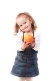 Niña bonita que sostiene una naranja aislada en blanco Foto de archivo
