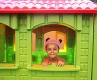 Niña bonita sonriente que juega en una casa del juego imagen de archivo