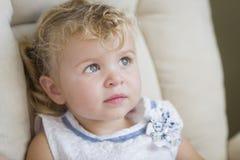 Niña cabelluda y azul observada rubia adorable en silla imagen de archivo
