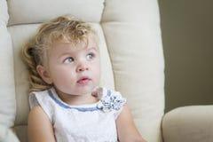 Niña cabelluda y azul observada rubia expresiva en silla Imágenes de archivo libres de regalías