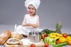 Niña caucásica en los huevos y el cazo de Uniform With Fresh del cocinero Fotos de archivo libres de regalías