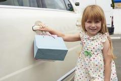 niña cerca de un coche blanco Imagen de archivo libre de regalías
