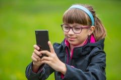 Niña cercana del retrato con el teléfono móvil Niña con la colocación y mandar un SMS con el teléfono Foto de archivo libre de regalías