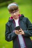 Niña cercana del retrato con el teléfono móvil Niña con la colocación y mandar un SMS con el teléfono Foto de archivo