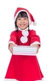Niña china asiática en el traje de santa que sostiene la caja de regalo Fotos de archivo libres de regalías