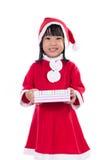 Niña china asiática en el traje de santa que sostiene la caja de regalo Imagen de archivo libre de regalías
