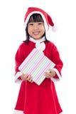 Niña china asiática en el traje de santa que sostiene la caja de regalo Imágenes de archivo libres de regalías