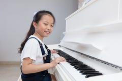 Niña china asiática feliz que juega el piano clásico en casa Foto de archivo