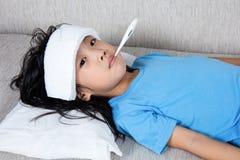 Niña china asiática que consigue la medida para el temperat de la fiebre Fotos de archivo