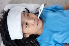 Niña china asiática que consigue la medida para el temperat de la fiebre Imagenes de archivo