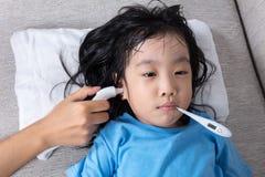 Niña china asiática que consigue la medida para el temperat de la fiebre Imagen de archivo