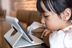 Niña china asiática que juega la tableta Foto de archivo libre de regalías