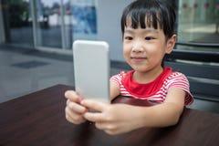 Niña china asiática que juega smartphone Imagen de archivo