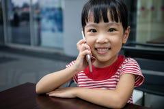 Niña china asiática que juega smartphone Imagen de archivo libre de regalías