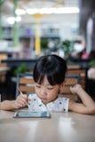 Niña china asiática que juega smartphone Fotografía de archivo