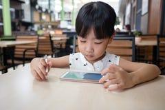 Niña china asiática que juega smartphone Foto de archivo