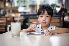 Niña china asiática que juega smartphone Fotografía de archivo libre de regalías
