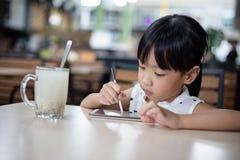 Niña china asiática que juega smartphone Fotos de archivo libres de regalías