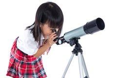 Niña china asiática que mira a través del telescopio Foto de archivo