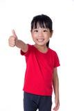 Niña china asiática que muestra los pulgares para arriba Imágenes de archivo libres de regalías